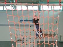 All-In Sport: Klimnet van oranje polypropyleen. Maaswijdte 25 cm. Levering met 4 bevestigingshaken met verankeringen.